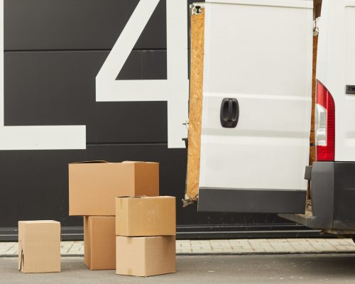 Image of van with opened door and cardboard boxes on the ground This is cargo delivery